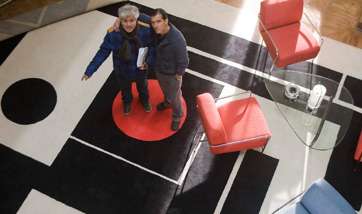 הבמאי והשחקן הראשי, אלמודובר ובנדראס, בחזרות לסרט. שולחן של נוגוצ'י מצד ימין, השטיח החד-פעמי הזה הוזמן ע''י הבמאי במיוחד לתפאורת הסרט. ההשראה שלו באה מהקונסטרוקטיביזם הרוסי. בסרט עצמו עומדת כאן ורה, עטופה וחבושה מכף רגל ועד ראש, ומאיימת בסכין על המנתח שנמצא בקומה העליונה ומשקיף עליה מבעד למדרגות (באדיבות קולנוע לב)