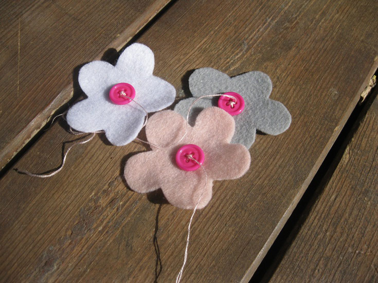 גוזרים מהלבד צורות של פרחים. תופרים את הכפתורים במרכז כל פרח (צילום: חן קרופניק)