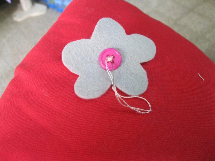תופרים את הפרחים על הכרית. אני בחרתי לתפור את הפרחים בקצה, כולם מרוכזים יחד. אפשר לתפור המון פרחים על כל הכרית או אפילו פרח אחד גדול במרכזה (צילום: חן קרופניק)