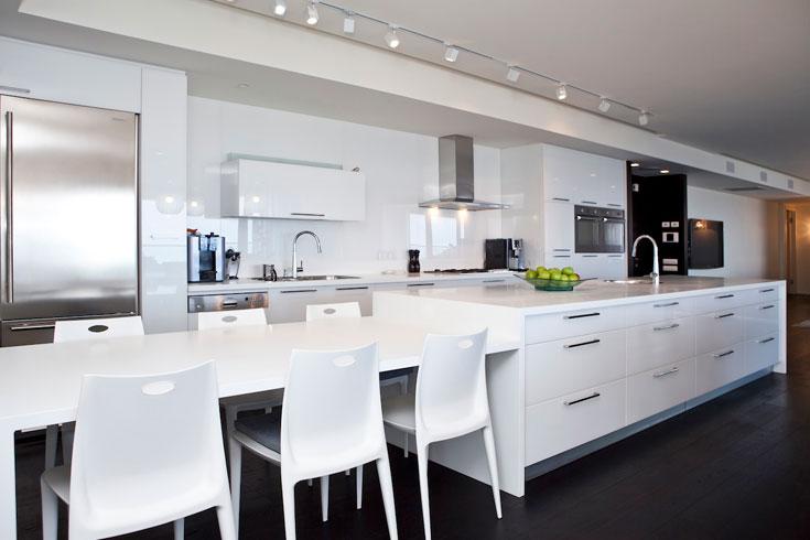 """דלתות זכוכית לבנות נטולות מסגרת מעניקות למטבח (''רגבה'') מראה עכשווי. קיר הארונות כולו חופה בזכוכית באותו גוון. ''קיבלתי את כל ההצעות של רותי ויעל, עד לדיון נוקב בסוגייה של  מדף לייבוש כלים מעל הכיור"""", מספרת בעלת הבית. ''הן רצו קו נקי ככל האפשר. המגמה הרווחת היום היא ראשית הצורה ורק אחר כך הנוחות, אבל התעקשתי על מייבש כלים שהוסתר בארון, ואני מרוצה"""" (צילום: שירן כרמל)"""