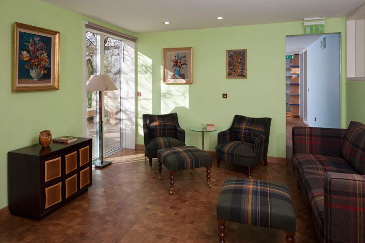 הכורסאות מרופדות בבד לבד משובץ, בסגנון בריטי טיפוסי, והקירות צבועים בגווני פסטל (צילום: Martine Hamilton-Wright)