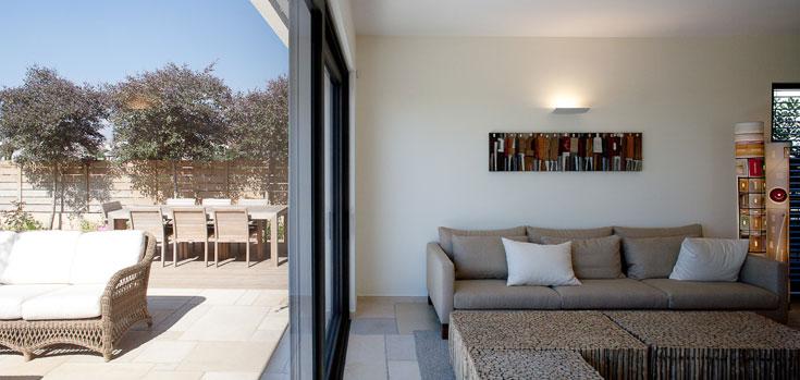 מעל לספה תבליט של האמנית הברזילאית מאיה פיאטי, ולצידה שתי מנורות מצוירות מברזיל. יחד הם מכניסים צבע לסלון (צילום: טל ניסים)