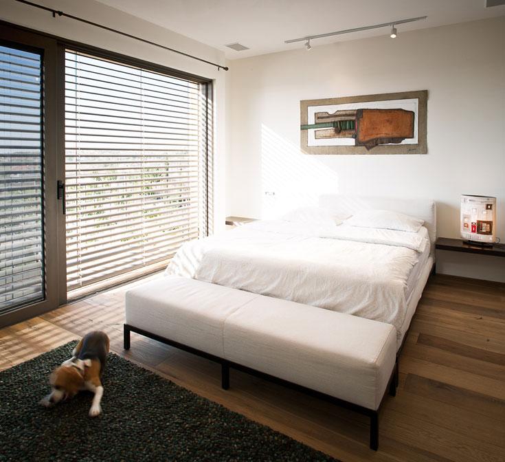 קומת חדרי השינה מחופה פרקט מעץ אלון. חדר ההורים צמוד למרפסת תלויה ומחופה דק. מעל המיטה עבודת אמנות צבעונית מברזיל, ועל הארץ שטיח צמר בגוני חום וירוק (''איתמר שטיחים''). על ארונות קיר ויתרו בינתיים, מאילוצי תקציב (צילום: טל ניסים)