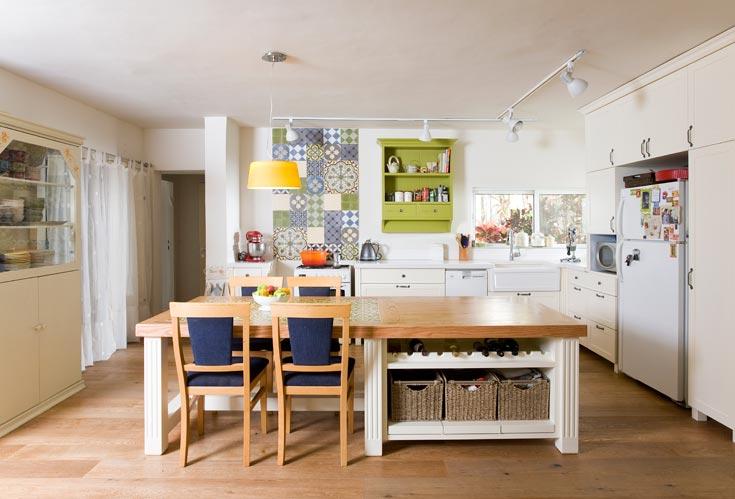 מטבח הבית, אחד משני החללים האהובים ביותר על בעלת הבית. מתחת לשולחן הגדול מקום לאחסון ומשמאל - וילון שקוף המסתיר מזווה (צילום: רני לוריא)