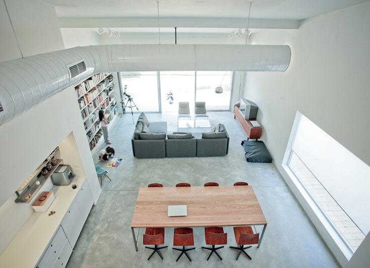 מבט מהגלריה לסלון: רצפת בטון שלא גוונה, ספות באפור כהה, שידת טלוויזיה משוק הפשפשים וכורסאות מהבית הקודם (צילום: טובי הוכשטיין)