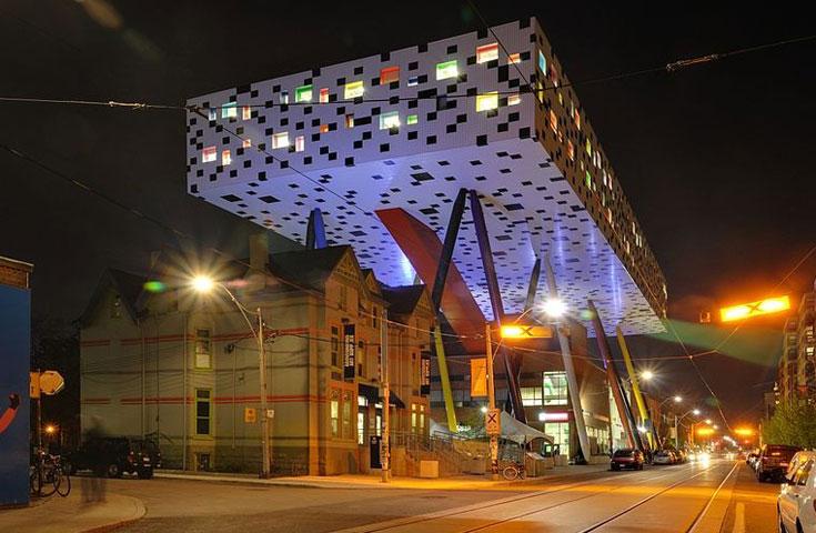 מרכז שארפ בטורונטו. אדריכל: וויל אלסופ. קובייה שנתמכת בעמודים דקים הניצבים בזווית, ובקורה האלכסונית האדומה (צילום: Taxiarcho228, CC)