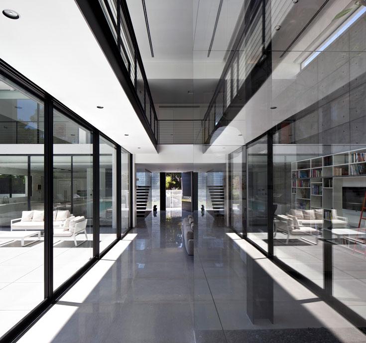 בין שני אגפי האירוח בקומה העליונה מפריד גשר, תחום בקיר הזכוכית הפונה לגינה  (צילום עמית גרון)