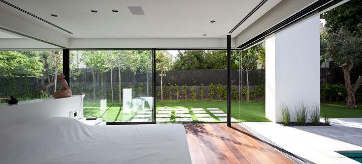 בין חדר השינה של ההורים לגינה הפרטית שלהם מפריד קיר זכוכית, שנתמך בעמוד פנימי ומאפשר לחלונות להיפתח לשני הצדדים (צילום עמית גרון)