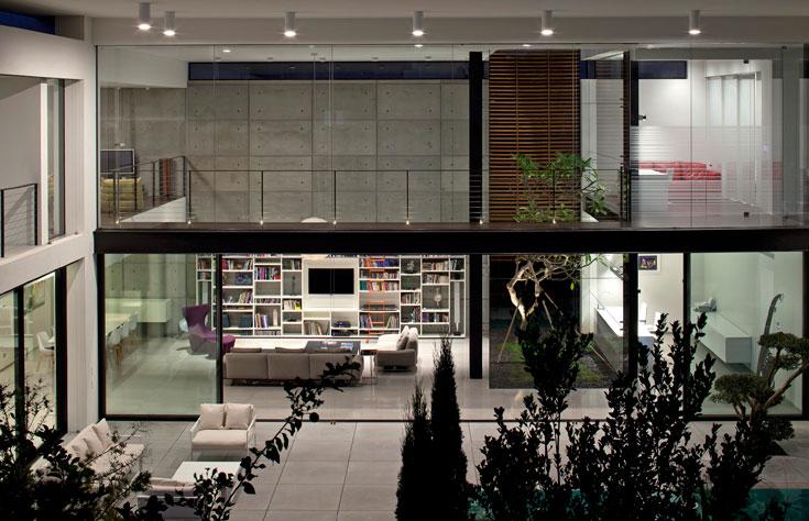 חלל הסלון המרכזי חופה בלוחות בטון חשוף. ספרייה גדולה מהווה אלמנט בולט (צילום עמית גרון)