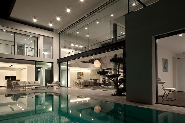 גג ''מרחף'' עוטף את הבית: הוא מנותק מהקומה העליונה באמצעות עמודים פנימיים ומצל על שטחי חוץ גדולים (צילום עמית גרון)